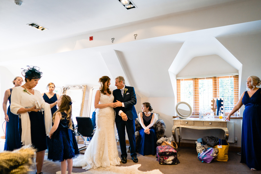 Bride with her father and family members at Nuthurst Grange Hotel in the bridal suite