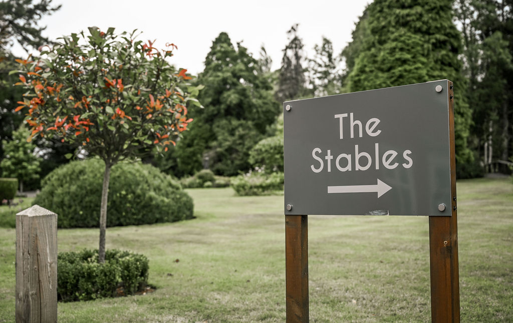 Sign pointing to the Stables barn function venue at Nuthurst Grange Hotel