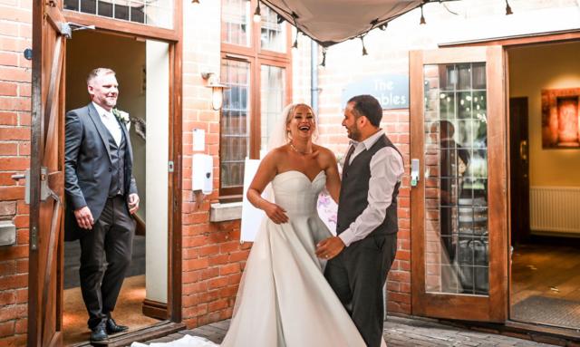 Wedding couple laughing with Mo at Nuthurst Grange