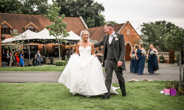 Happy wedding couple outside the Stables barn at Nuthurst Grange Hotel