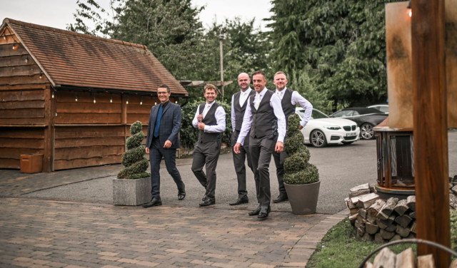 Groom and his best men walking toward the Stables barn at Nuthurst Grange