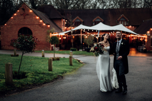 Laughing wedding couple outside the Stables barn at Nuthurst Hotel