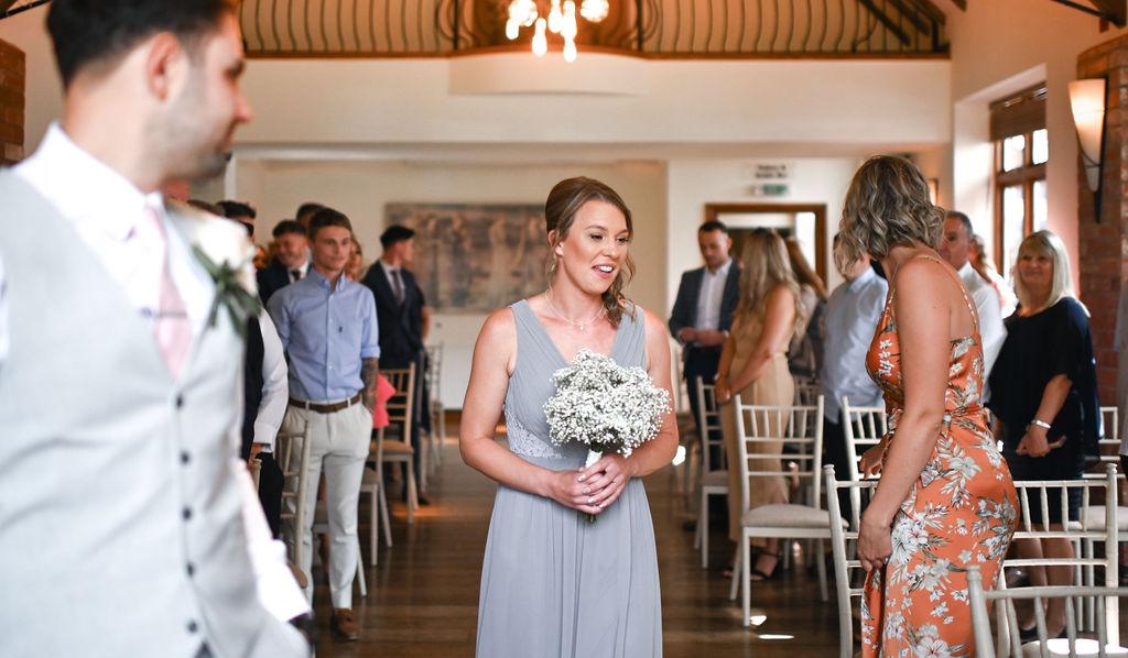 Bridesmaid smiling at Nuthurst Grange hotel