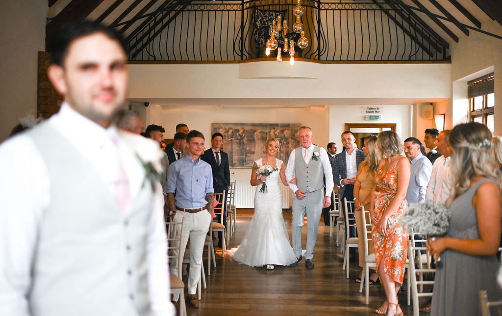 Bride is walking down the aisle with her father at Nuthurst Grange Hotel