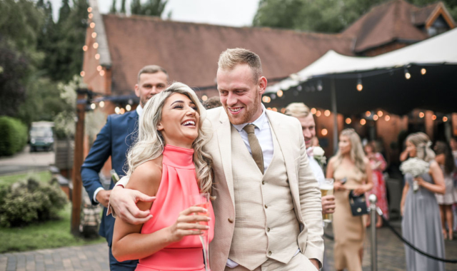 Elegant couple laughing outside the Stables at Nuthurst Grange