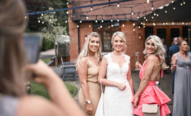 Bride and her friends are smiling at the camera at Nuthurst Grange